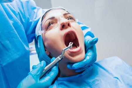 Dentist using surgical pliers to remove a decaying tooth.