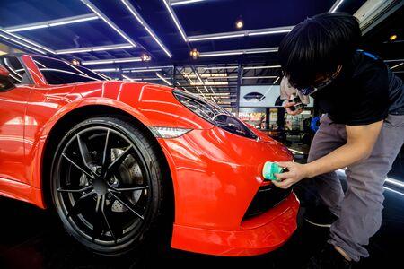 Car service worker applying nano coating on a car detail Foto de archivo