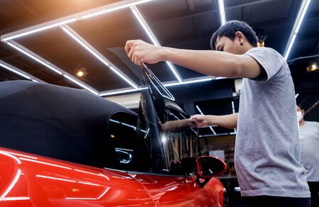 Applying tinting foil on a car window in a auto service Imagens