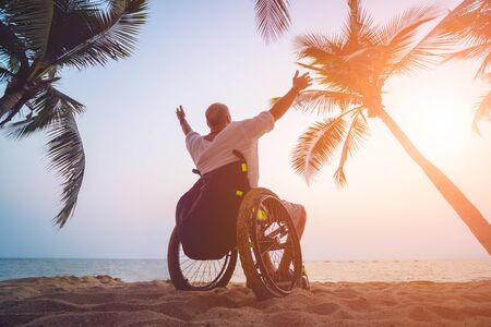 Disabled man in a wheelchair on the beach. Concept background Imagens
