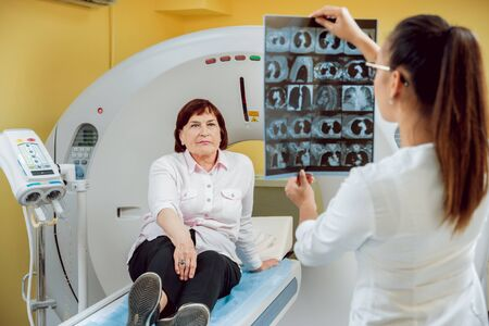 Radiologist with an elderly female patient looking at x-ray.