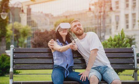 一对年轻夫妇在街上使用虚拟现实眼镜玩游戏。