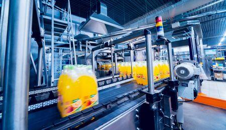 Machine de cerclage pour ligne d'emballage. Machine moderne pour ligne d'emballage en usine. Technologie et concept industriel. Fond