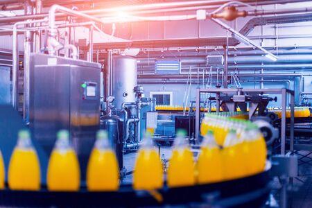 Intérieur de l'usine de boissons. Convoyeur avec bouteilles de jus ou d'eau. Des équipements modernes Banque d'images