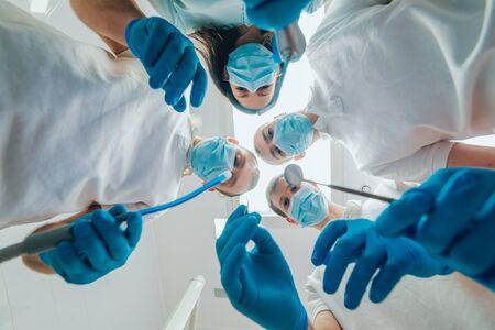 Four dentist in uniform perform dental implantation operation