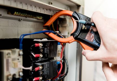 The man is repairing the switchboard voltage with automatic switches. Electrical background Stock Photo