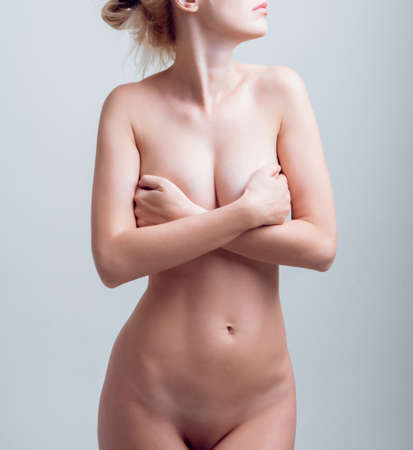 Beautiful naked girl in the studio. Light background Archivio Fotografico
