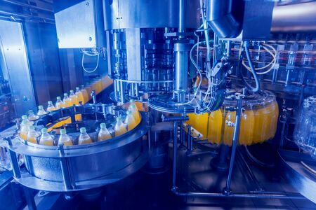 Automatic filling machine pours water into plastic PET bottles. Brewing production. Industrial background.
