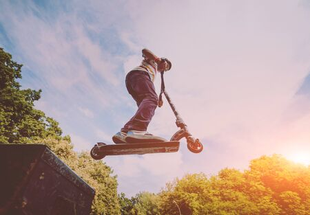 Boy riding a kick scooter in a park. Beautiful background Stock Photo