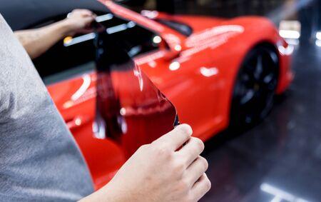 Applying tinting foil on a car window in a auto service Reklamní fotografie
