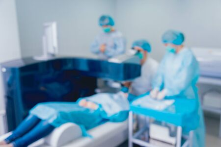 Laser vision correction. A patient and team of surgeons in the operating room during ophthalmic surgery. Eyelid speculum. Lasik treatment. Patient under sterile cover