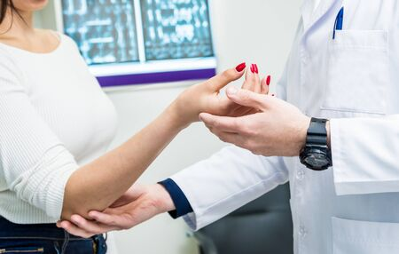 Traumatologist examining patient hands in modern hospital. Medical background