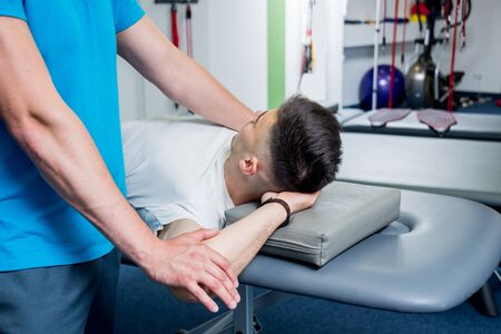Rehabilitation therapy. Physiotherapist working with young male patient in the rehabilitation center. Treatment pain in spine Фото со стока