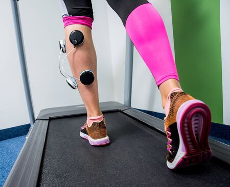 Young sports woman with electrostimulator on the muscles of the legs. Standard-Bild