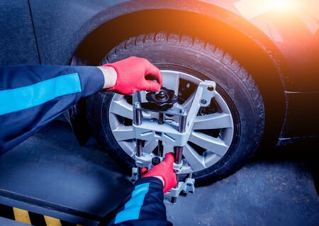 Car mechanic installing sensor during suspension adjustment.
