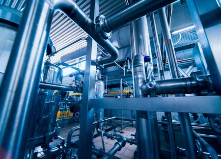 Modern interior of a brewery. Barrels and pipes. Factory interior. Industry background Imagens