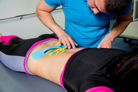 Kinesiotaping. Physical therapist applying tape to young beautiful womans spine.