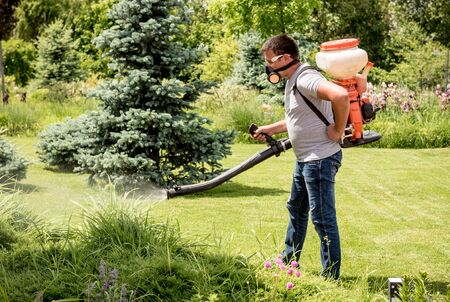 Gardener in protective mask and glasses spraying toxic pesticides trees Foto de archivo