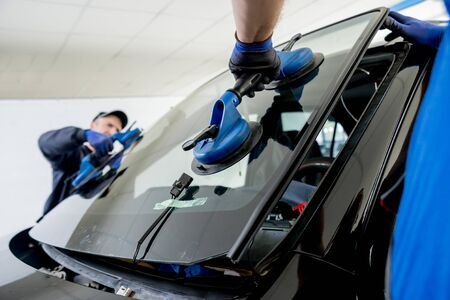Travailleurs spéciaux de l'automobile remplaçant le pare-brise ou le pare-brise d'une voiture dans le garage de la station-service automobile. Fond Banque d'images
