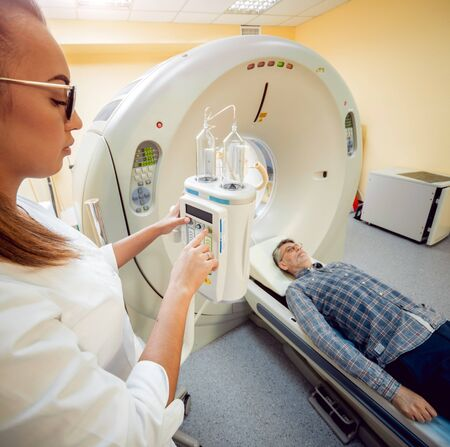 Doctor and patient in the room of computed tomography at hospital. Medical equipment.
