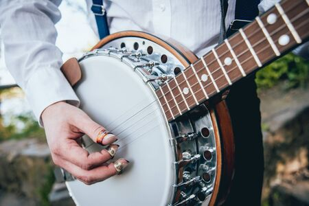 View of musician playing banjo at the street. Authentic background