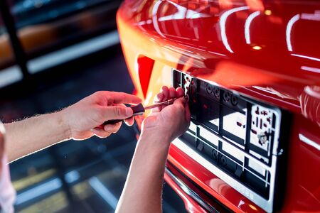 Technician changing car plate number in service center. Light background