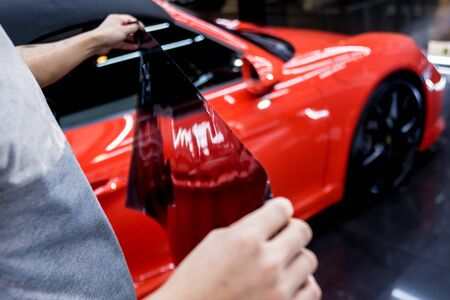 Applying tinting foil on a car window in a auto service. Red car at background Imagens