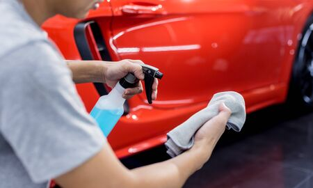 Car service worker polishing car wheels with microfiber cloth. Tools for polishing
