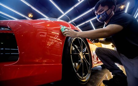 Car service worker applying nano coating on a car detail. Tools for polishing Banque d'images