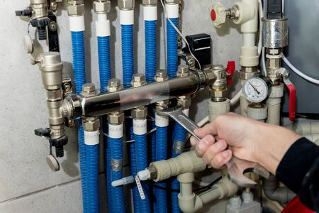 Heating engineer fixing modern heating system in boiler room. Automatic control unit. Engineering systems for home.