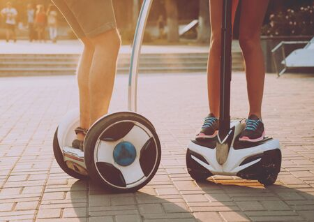Young couple driving on monowheel in the park. Banco de Imagens