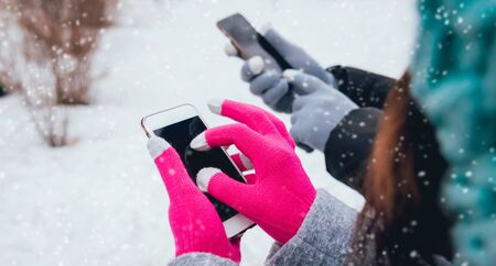 Couple using smartphone in winter with gloves for touch screens. Backgound