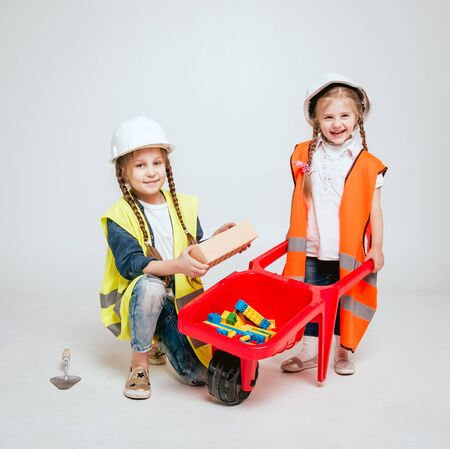 Little girls on the white background. Construction