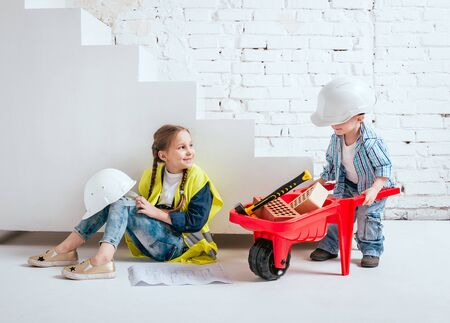 Little girl and boy with wheelbarrow on the white background. Construction