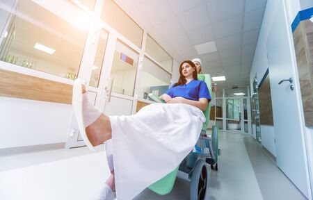 Nurse moves mobile medical chair with patient at hospital. Medical equipment.