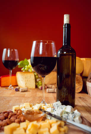 Cheese and wine on a dark table. Beautiful background 写真素材