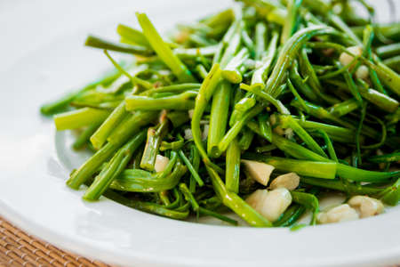 Boiled greens with rice on the white plate.