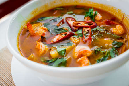 Seafood soup Tom Yam on the white plate.