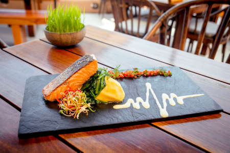 Fish with vegetables on a black plate. 写真素材
