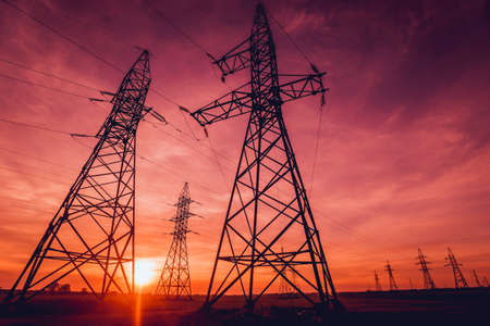 High-voltage power lines at sunset. Electricity distribution station. Background
