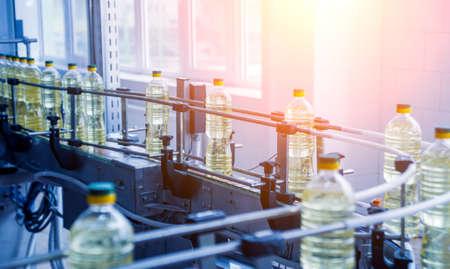 Bottling line of sunflower oil in bottles. Vegetable oil production plant.