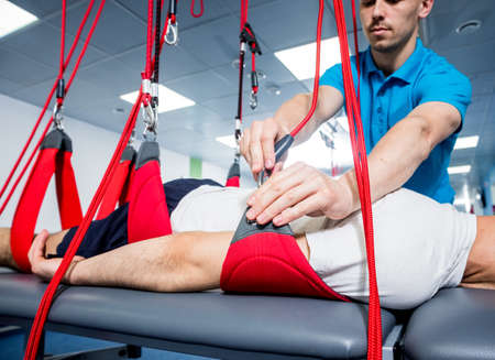 Physiotherapy. Suspension training therapy. Young man doing fitness therapy
