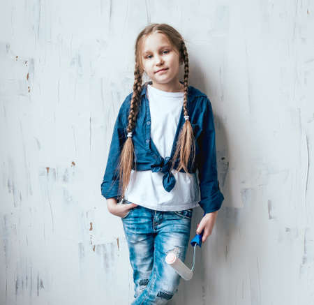Little girl in a room with a wooden wall. Construction