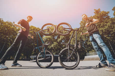 Bmx riders performing tricks at skatepark. Outdoors