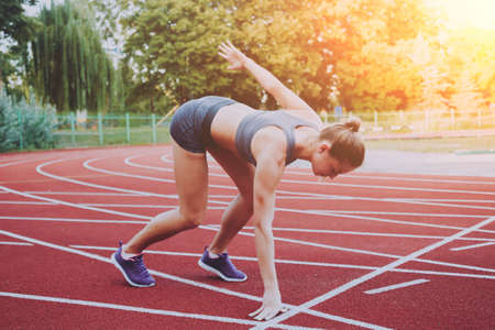 Female athlete in position ready to run.