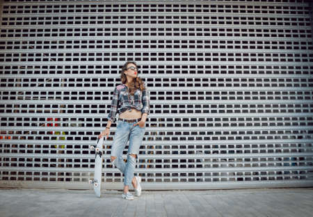 Young girl with skateboard on the background of the big gray wall.