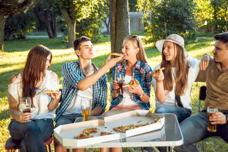 Cheerful friends on picnic in the park. Eating pizza Stock Photo