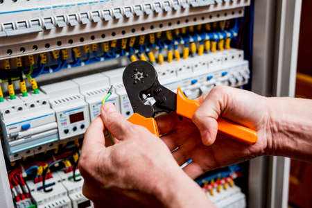 The man is repairing the switchboard voltage with automatic switches. Electrical background Banque d'images