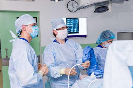 Arthroscope surgery. Orthopedic surgeons in teamwork in the operating room