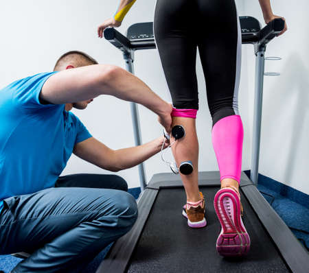 Physical therapist install electrostimulator on the muscles of the legs
